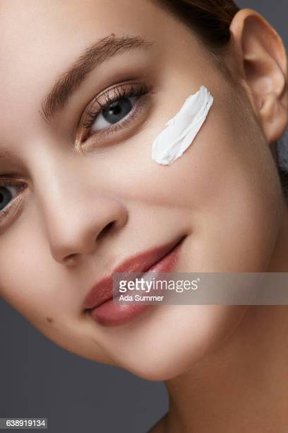 close up of woman with anti aging cream on her cheek