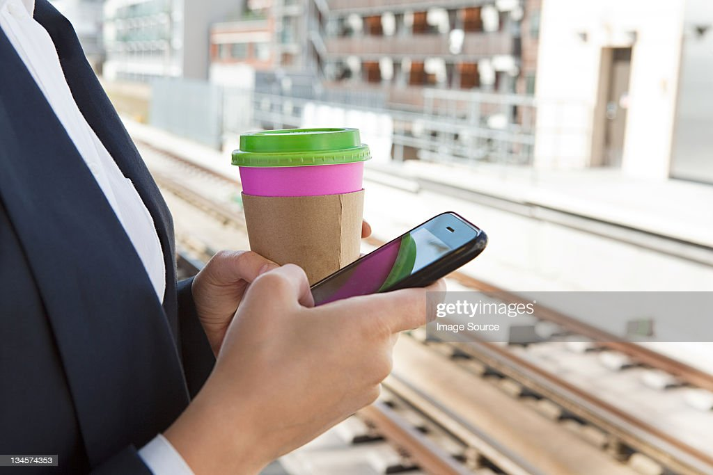 Close up of woman with coffee and smart phone in train station : Stock Photo