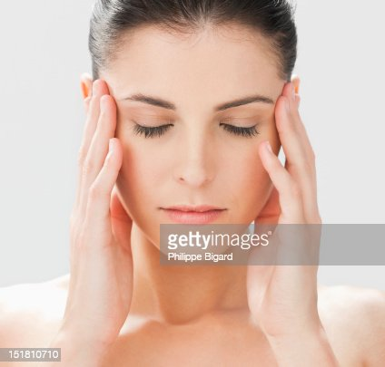 Close up of woman with head in hands and eyes closed : Stock Photo