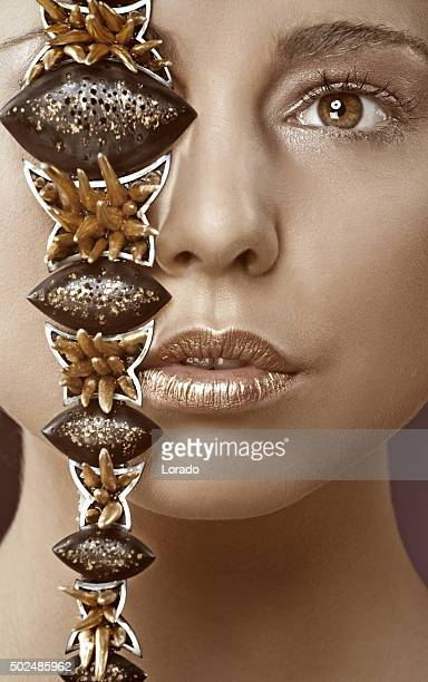 close up of woman with jewellery in front of her face
