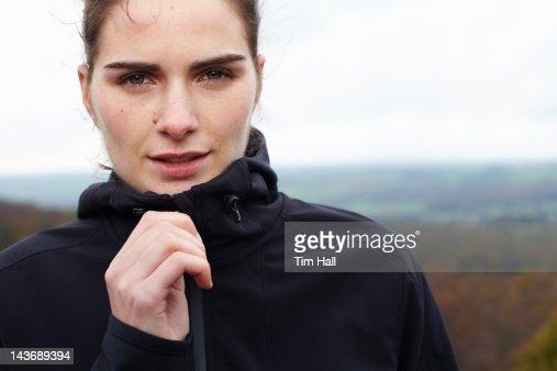 Close up of woman zipping up coat