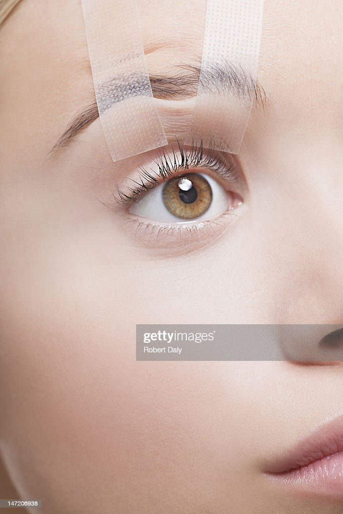Close up of woman's eye taped open : Stock Photo