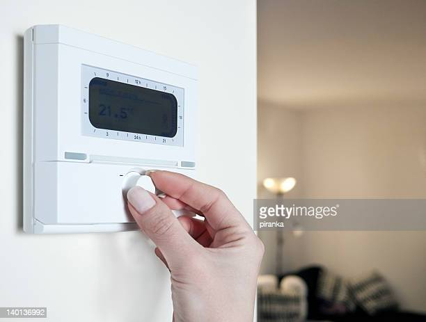 Close up of woman's hand adjusting the thermostat