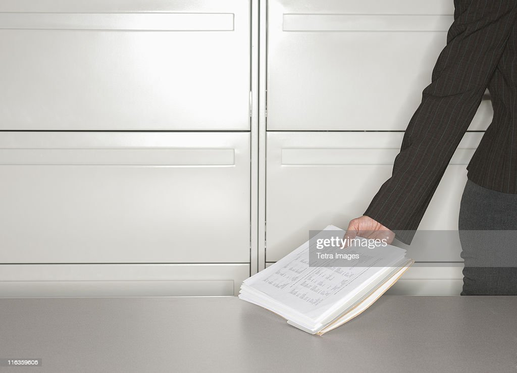Close up of woman's hand in office holding documents : Stock Photo