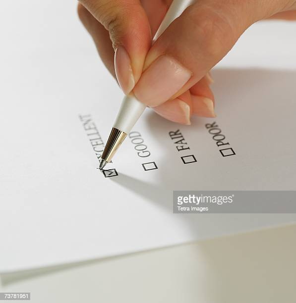 Close up of woman's hand marking check box with pen