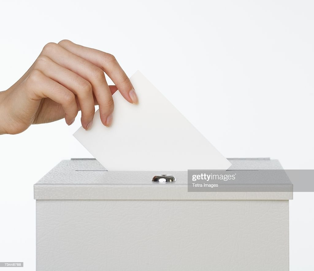 Close up of woman's hand putting card in box with slot : Stock Photo