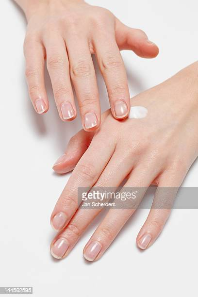 Close up of woman's hands applying  moisturizer, studio shot