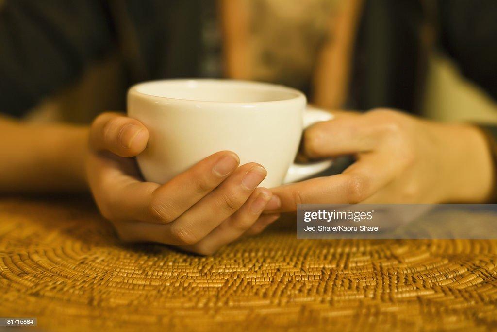 Close up of woman's hands holding tea mug : Stock Photo