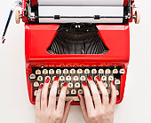 Close up of woman's hands with red nail polish typing on antique typewriter