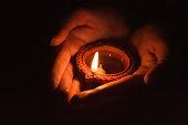 Woman holding diya dip dipak oil lamp on hand in dark background