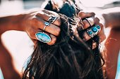 Close up of Women with bohemian style jewelery rings on hands