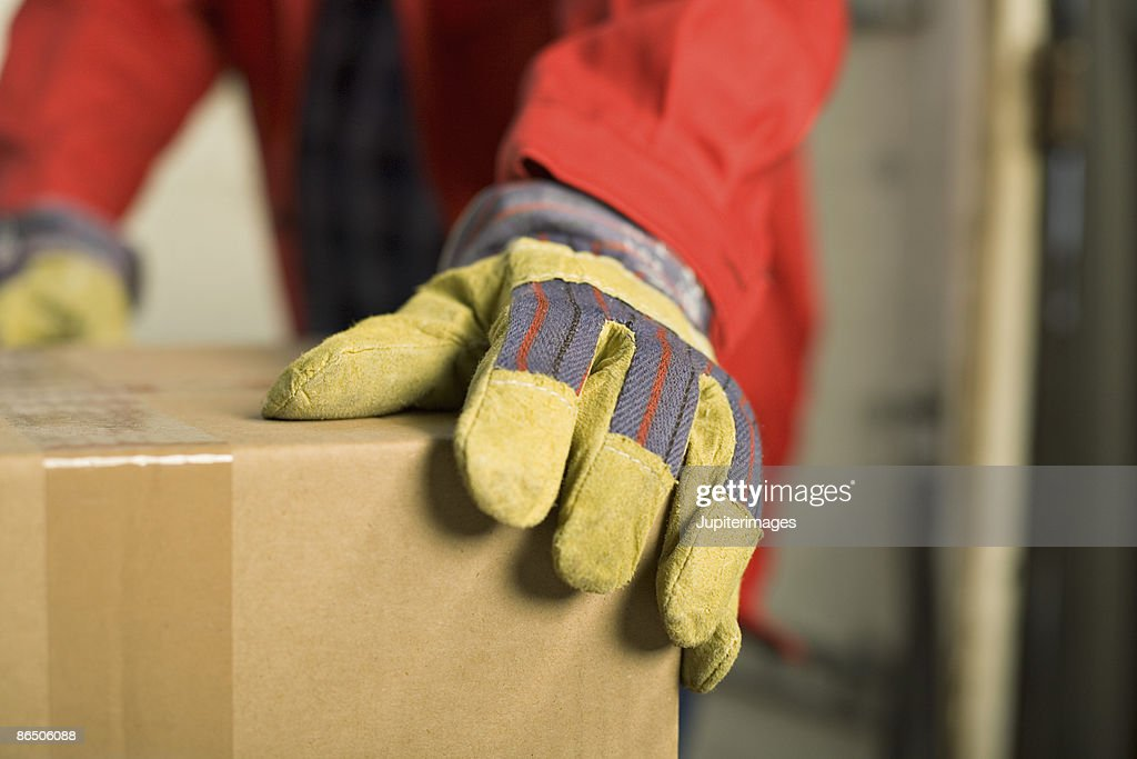 Close up of worker's glove and box