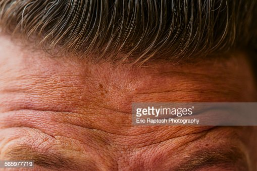 Close up of wrinkled forehead of Caucasian man