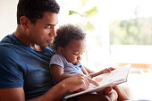 Close up of young adult black father reading a book with his two year old son, close up, side view, backlit