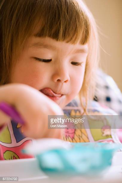 Close up of young girl eating in high chair