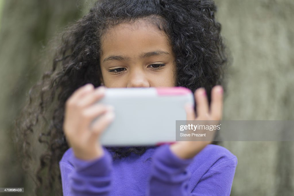 Close up of young girl in park playing hand held video game : Stock Photo