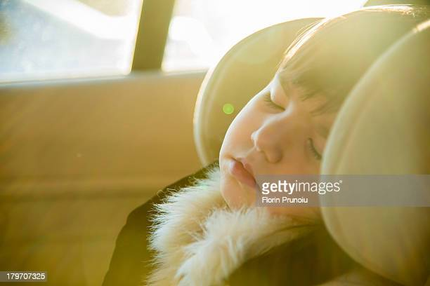 Close up of young girl sleeping in car