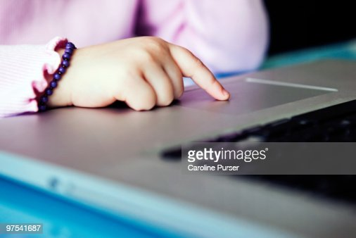 Close up of young girl's hand on laptop : Stock Photo