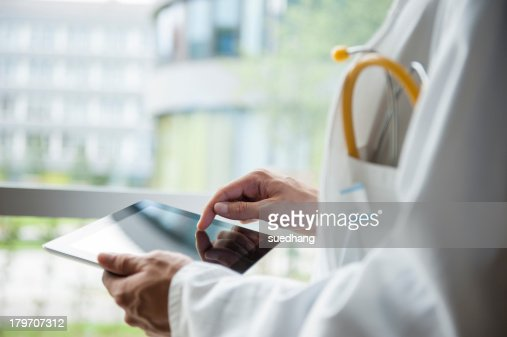 Close up of young male doctor using digital tablet