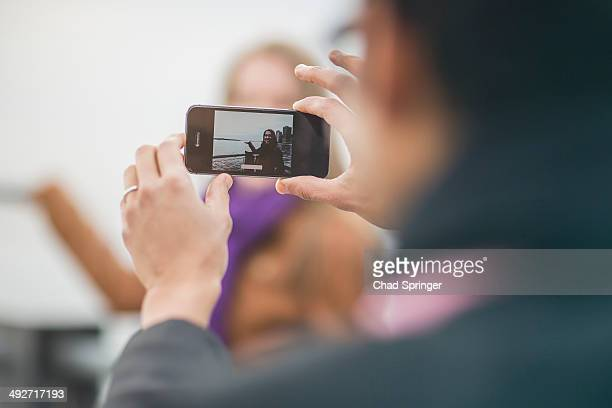 Close up of young man photographing girlfriend on camera phone