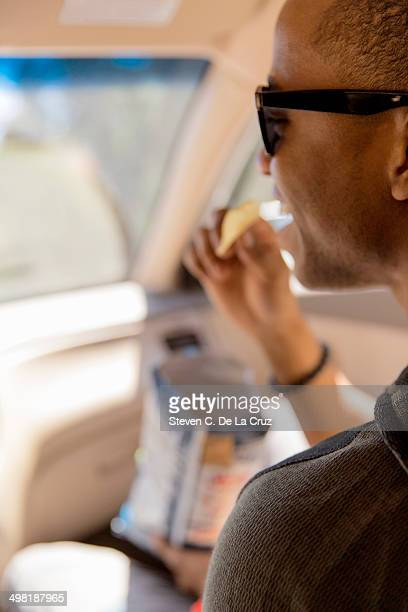 Close up of young man reading snacking on crisps in car