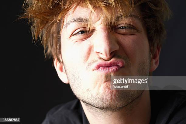 Close up of young man with messy hair against black background, pouting, portrait