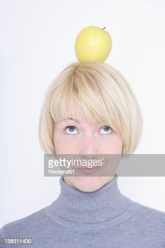 Close up of young woman balancing fruit on head against white background