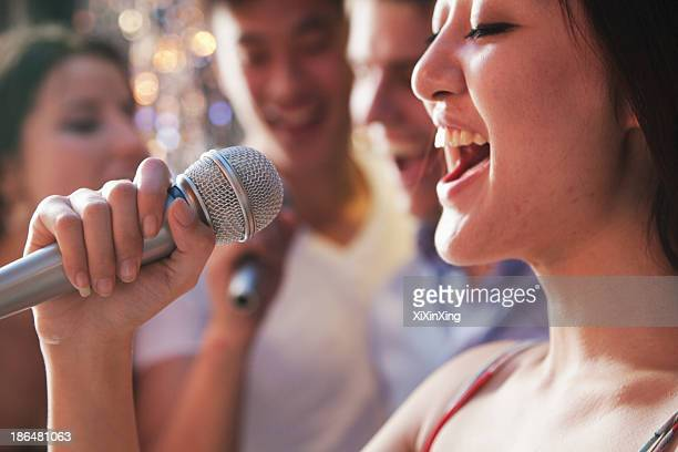 Close- up of young woman holding a microphone and singing at karaoke, friends singing in the background
