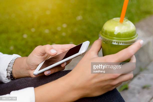 Close up of young woman sitting with smoothie drink using smartphone