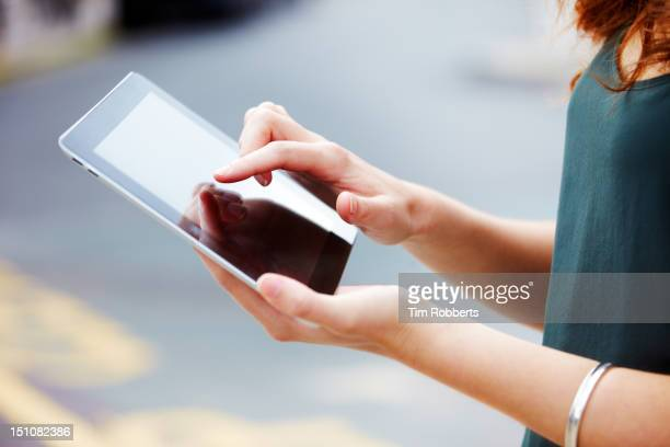 Close up of young woman using digital tablet.
