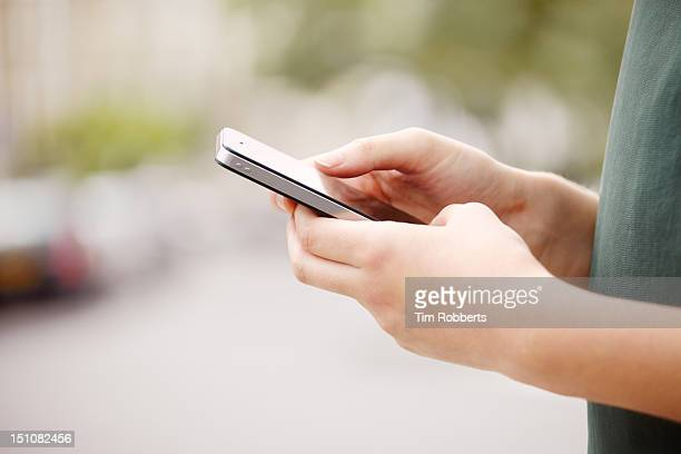 Close up of young woman using smart phone.