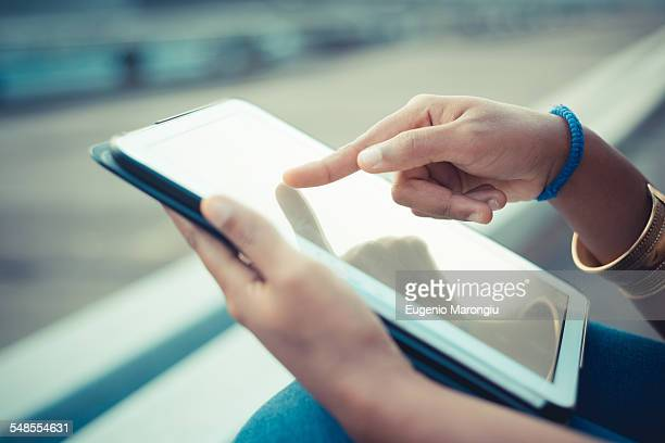 Close up of young womans hands using touchscreen on digital tablet