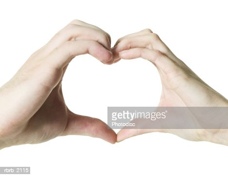 close up on a pair of female hands as they make the symbol of a heart : Stock Photo