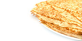 Close up on a stack of crepes (french pancakes) on a plate, white background