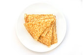 Close up on a stack of folded crepes (french pancakes) on a plate, white background