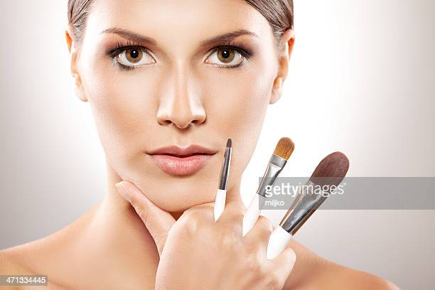Close up on beautiful woman holding make-up brushes