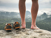 Close up on Blister on foot of a male. Hurt hikers legs without shoes. Misty morning fall nature. Outdoor activities