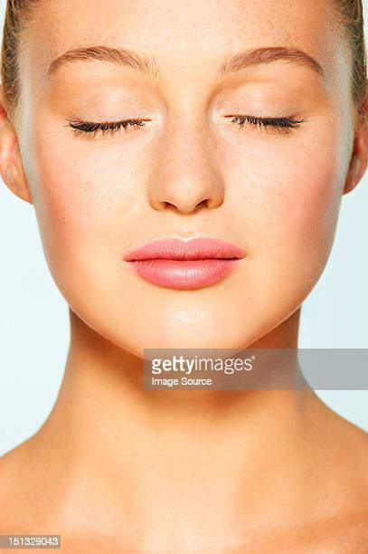 Close up on face of young woman with eyes closed