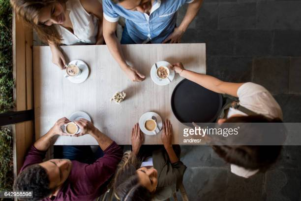 Close up on group of friends at a coffee shop