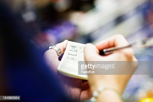 Close up on hands as woman checks shopping list