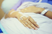 close up on patient woman hand sleeping on bed after surgery operation and wait doctor,nurse to diagnosis syndrome later , healthy living concept