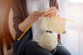 Close up on woman's hands knitting. Sitting on old armchair near window
