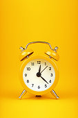 Close up one small yellow metal twin bell retro alarm clock over warm yellow paper background with copy space, low angle front view