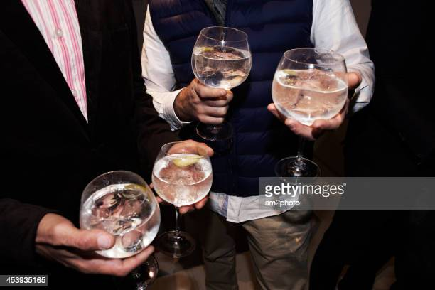 Close up people carrying 4 gintonic glasses