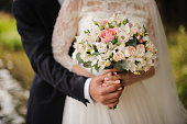 Close up photo of a bridegroom embracing a bride holding a beautiful bouquet of flowers