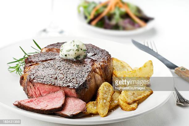 Close up photo of a medium rare steak with potato sidings