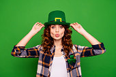Close up photo of cool attractive she her lady holding hands cap sending kiss to ireland people wearing casual checkered plaid shirt leprechaun headwear isolated on green bright vivid background