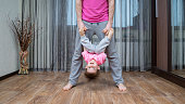 Father stands and holds the the boy's hands. Boy hangs upside down. They dressed in same color clothes.