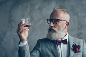 Close up photo of serious pensive confident satisfied bearded rich wealthy entrepreneur wine-maker manufacturer looking at the glass with whisky, isolated on grey background