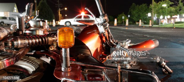 Close up photograph of a crashed motorcycle and police car
